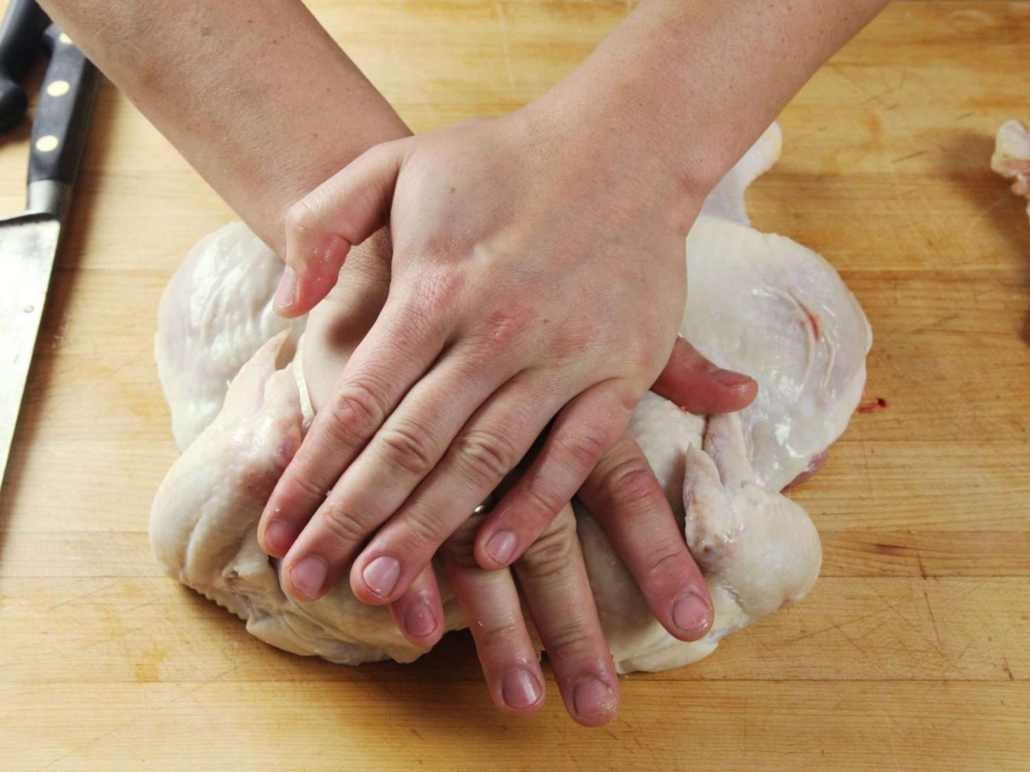 Using two hands to press down on the breastbone of a raw chicken to spatchcock it.
