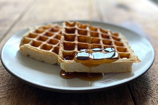 Two sourdough waffles on a plate with maple syrup