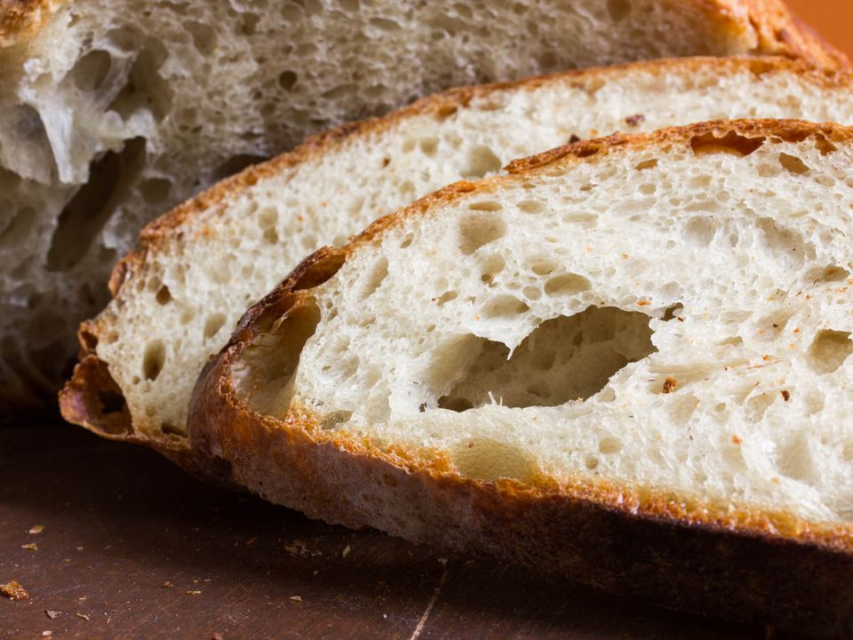 A close up of two slices of artisanal bread, with the rest of the loaf in the background.