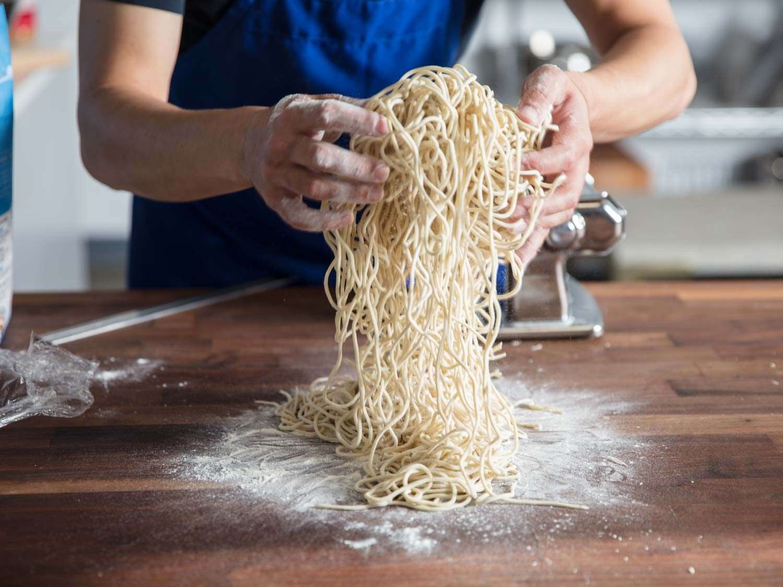 Shaking off excess flour from cut ramen noodles