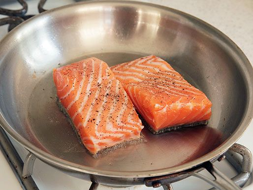 Pan-roasting salmon fillets in a stainless steel skillet.