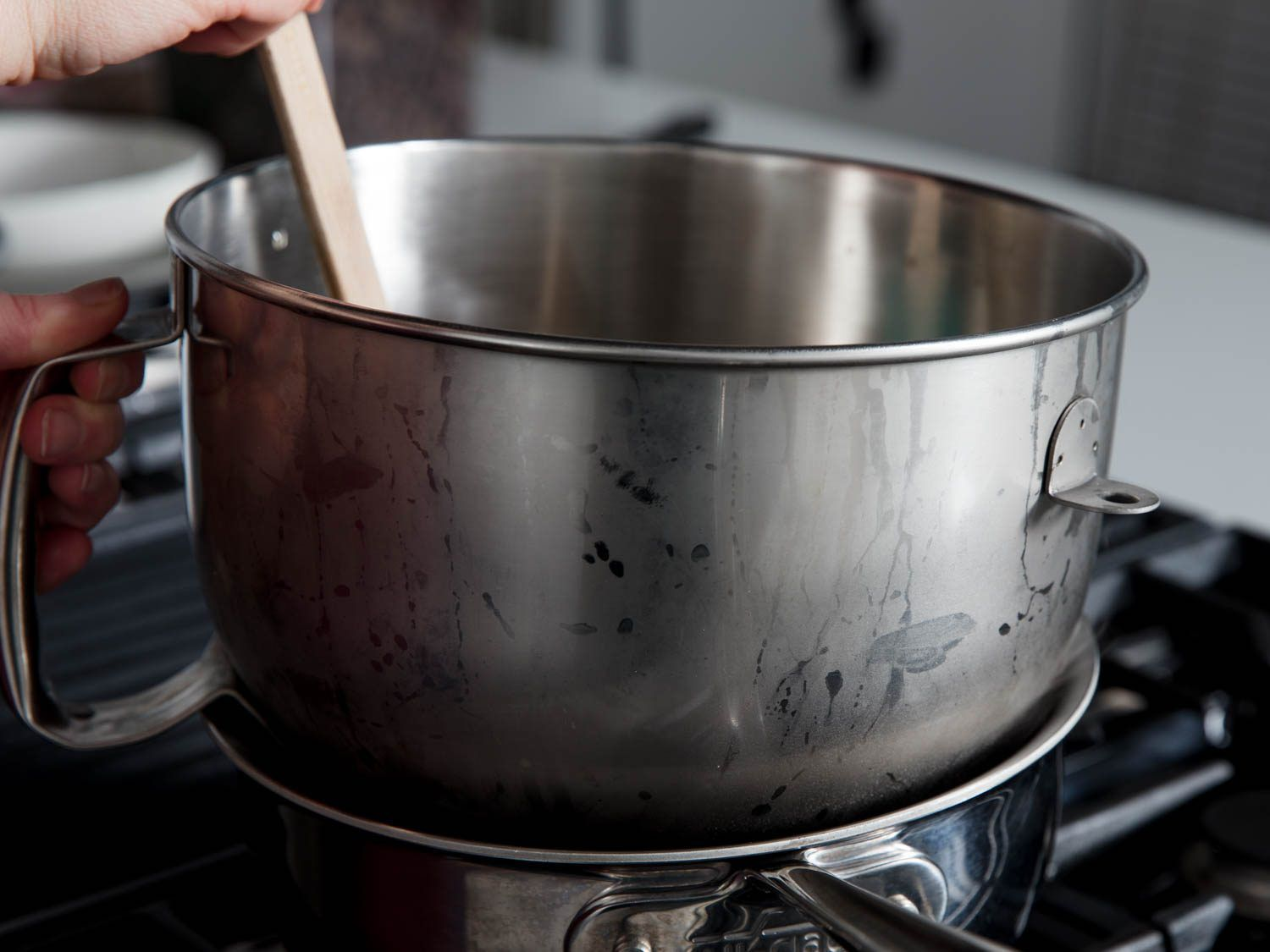 a stand mixer bowl placed over a water bath