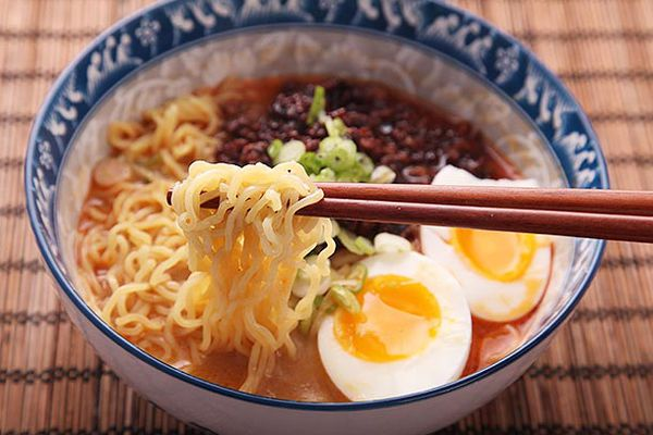 A bowl of prepared ramen from Sun Noodles. The ramen has a two soft-boiled egg halves, green onions, and broth. A pair of chopsticks are lifting some of the noodles.