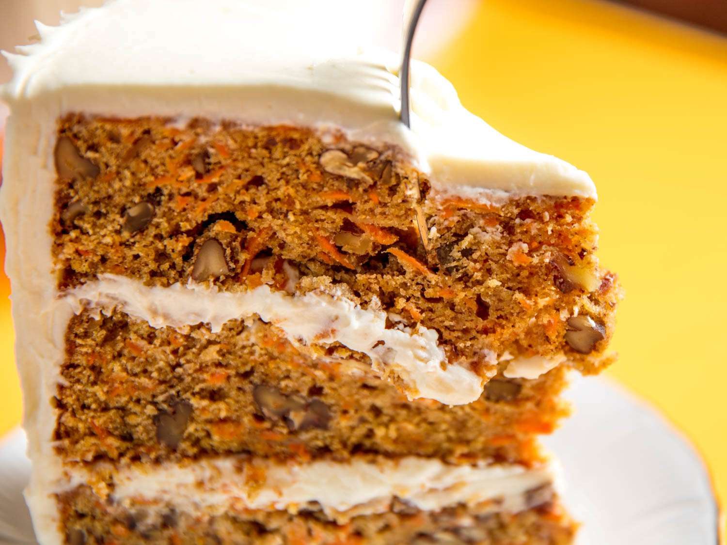 Close-up of a fork cutting into a wedge of carrot layer cake