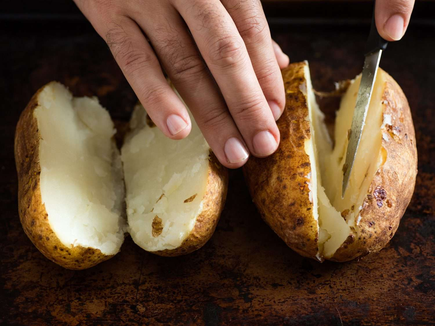 Using a pairing knife to cut two potatoes in half.