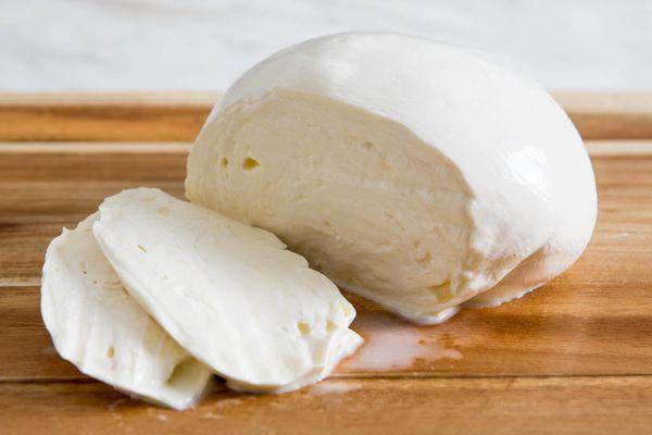 A partially sliced ball of homemade fresh mozzarella cheese on a wooden cutting board.