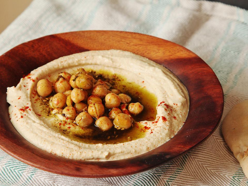 Extra-creamy Israeli-style hummus in a shallow wooden bowl, topped with cooked chickpeas, olive oil, za'atar, and paprika.