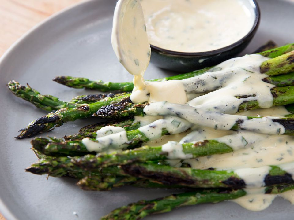 Side view of miso béarnaise being spooned over charred asparagus.