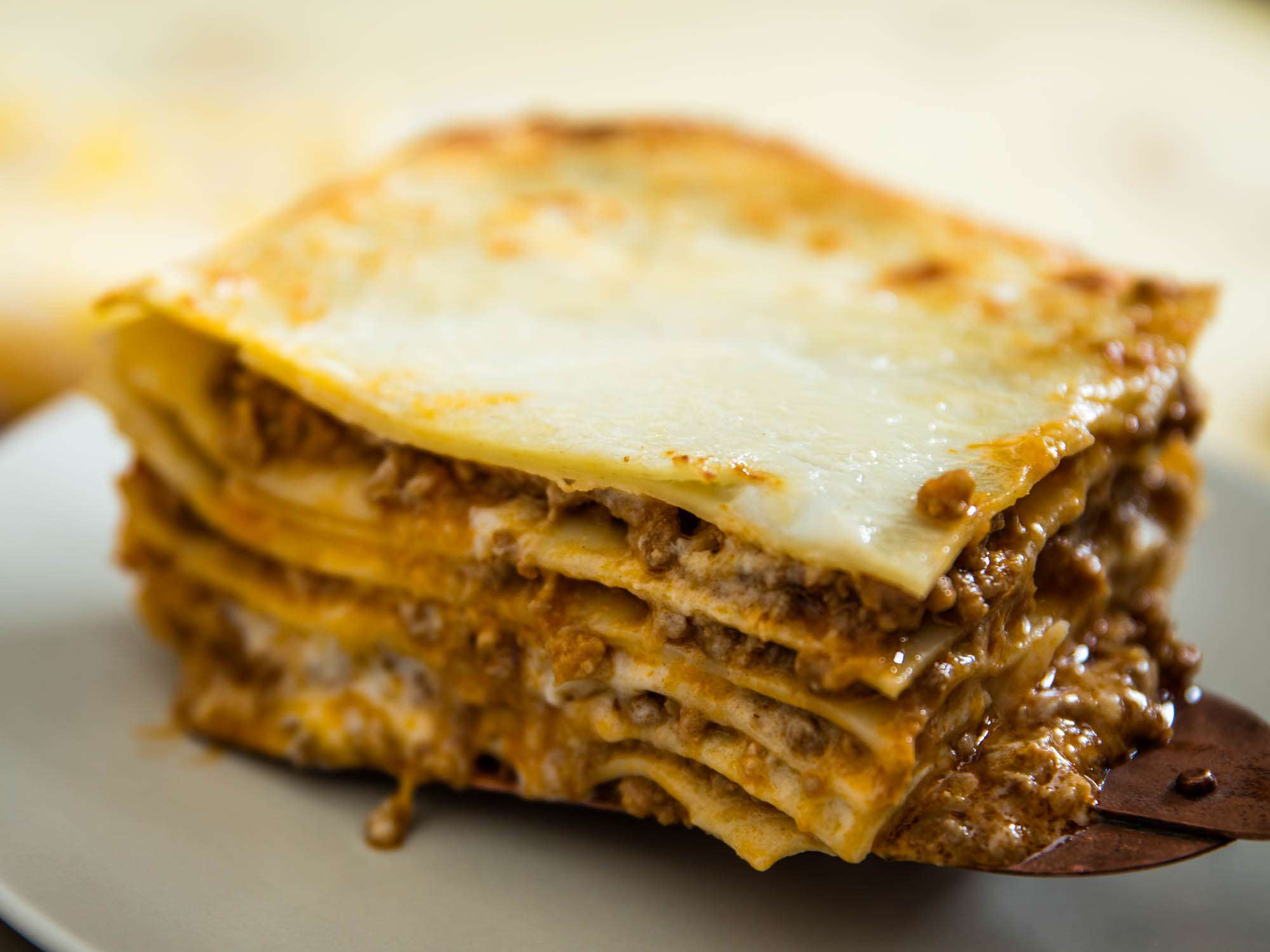 A serving of lasagna bolognese being placed on a plate.