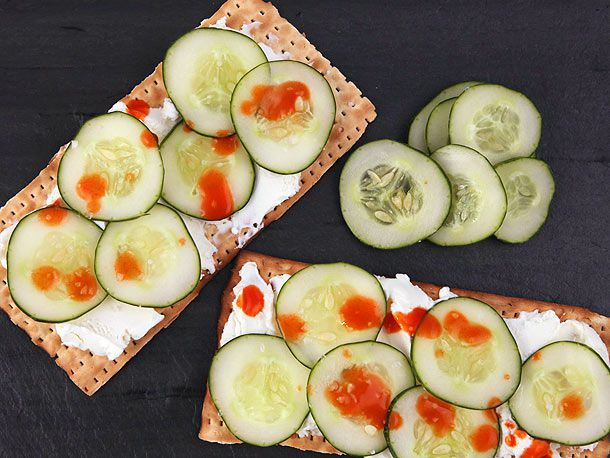 Two pieces of matzo spread with goat cheese and topped with sliced cucumber and dots of sriracha, next to a few more slices of cucumber