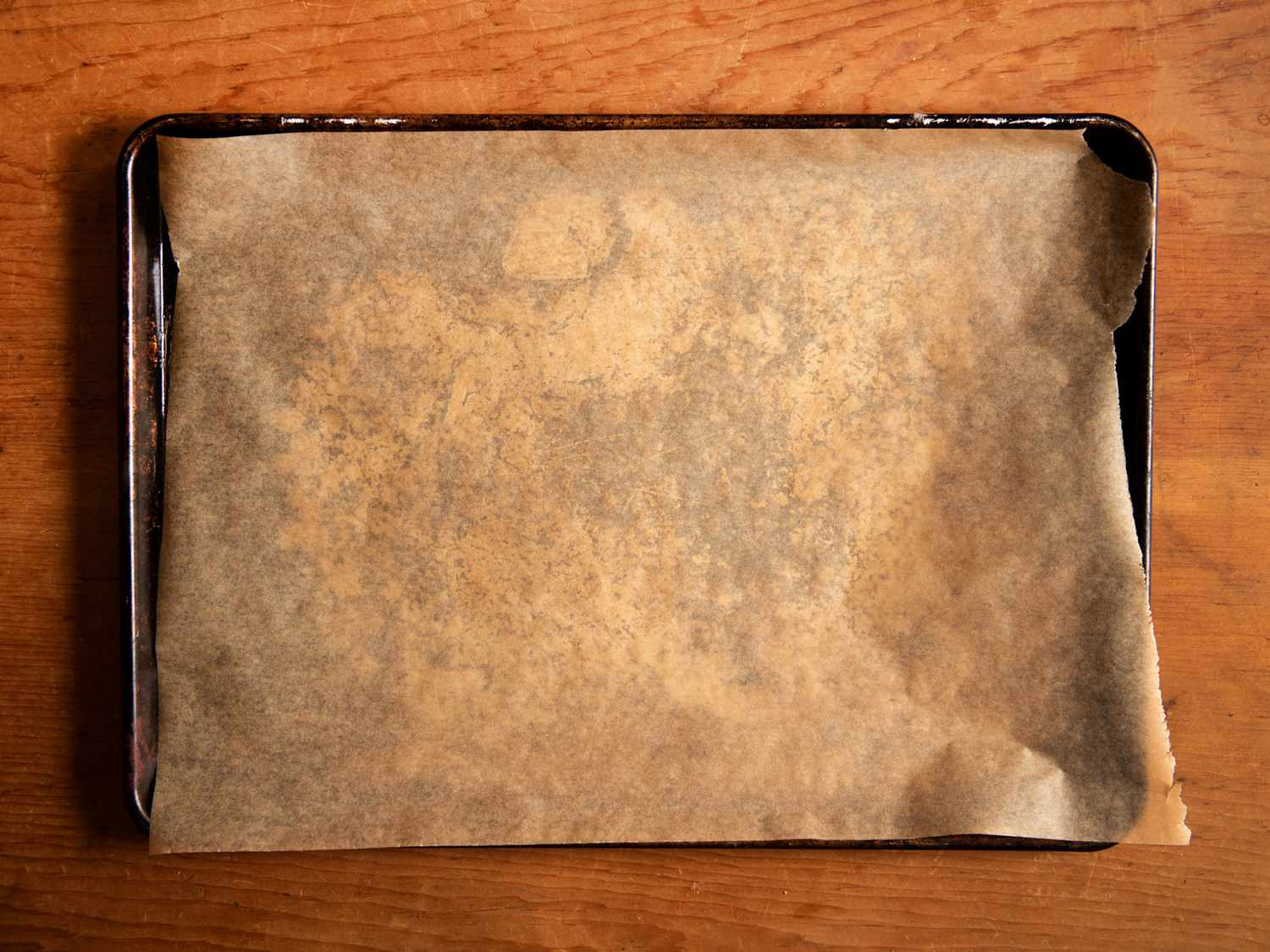 A rimmed baking sheet lined with parchment paper on a wood counter.