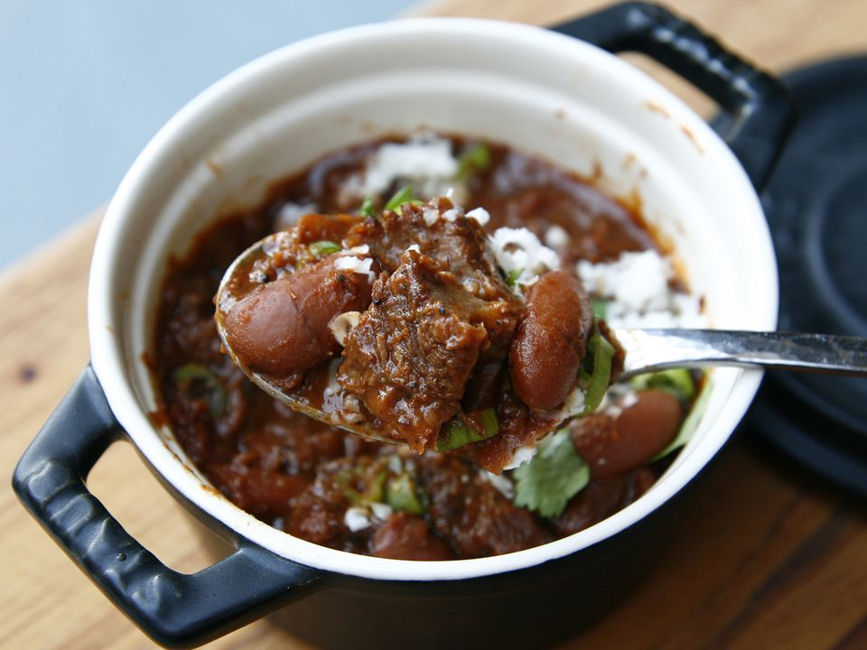 Spoon pulling bite of beef chili out of a small bowl, showing tender beans and short rib meat.