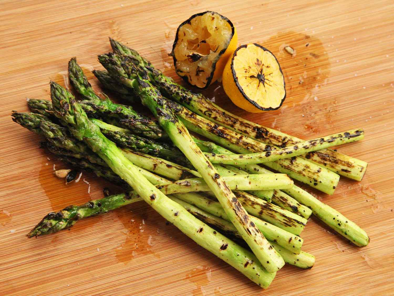 Grilled asparagus spears on a cutting board with charred lemon halves.