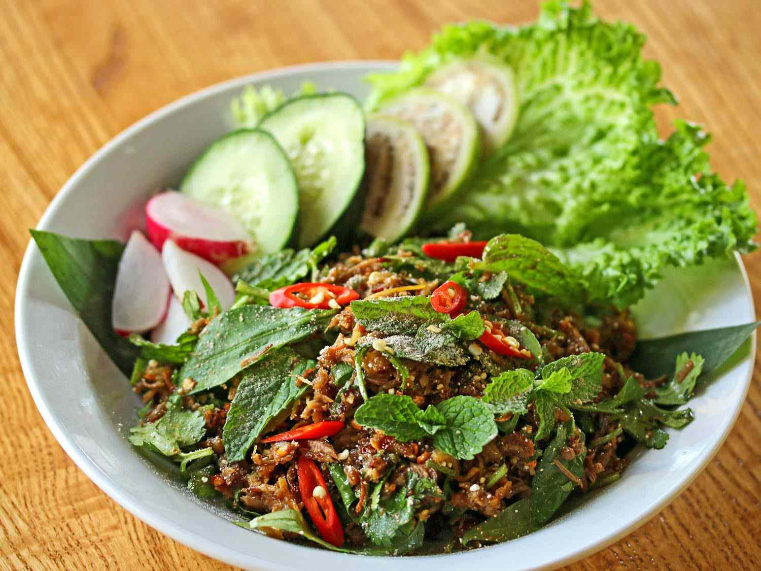 A bowl of laab ped, a salad of ground duck meat, chilies, and herbs, topped with whole mint leaves, with lettuce, cucumber, and radish on the side