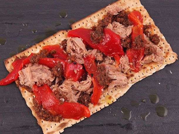 A piece of matzo layered with tuna, roasted red peppers, and olive tapenade