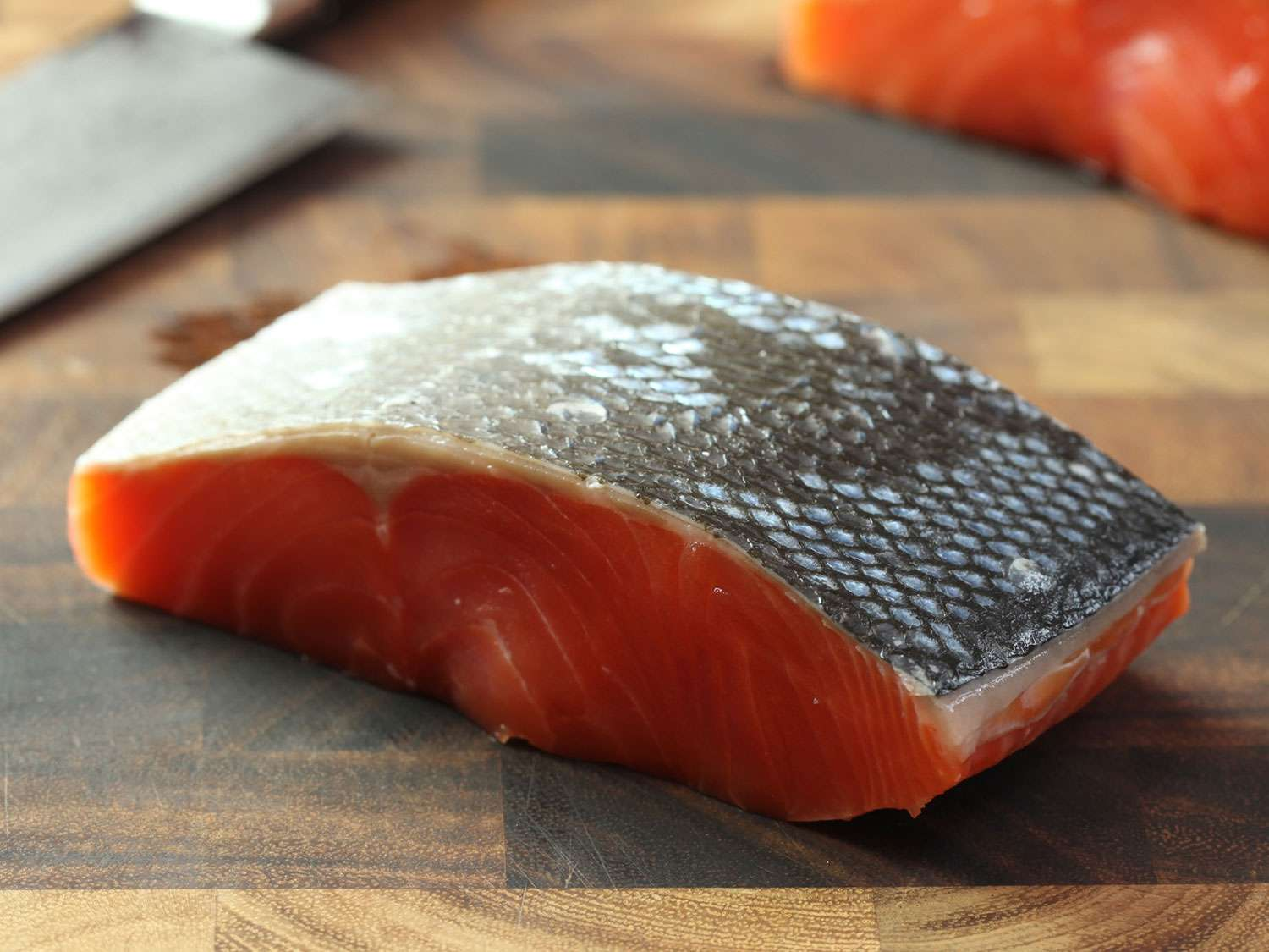 Raw, skin-on salmon fillet sitting skin-side up on a wooden cutting board.