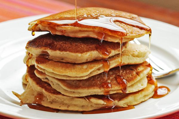 A stack of five pancakes on a plate with syrup being drizzled over them.