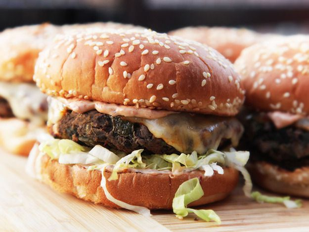 Homemade black bean burgers on buns with sauce and shredded lettuce