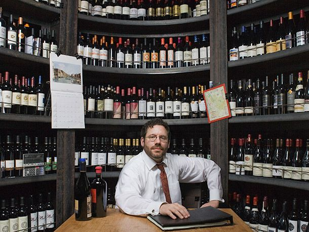 sommelier in front of shelves of wine