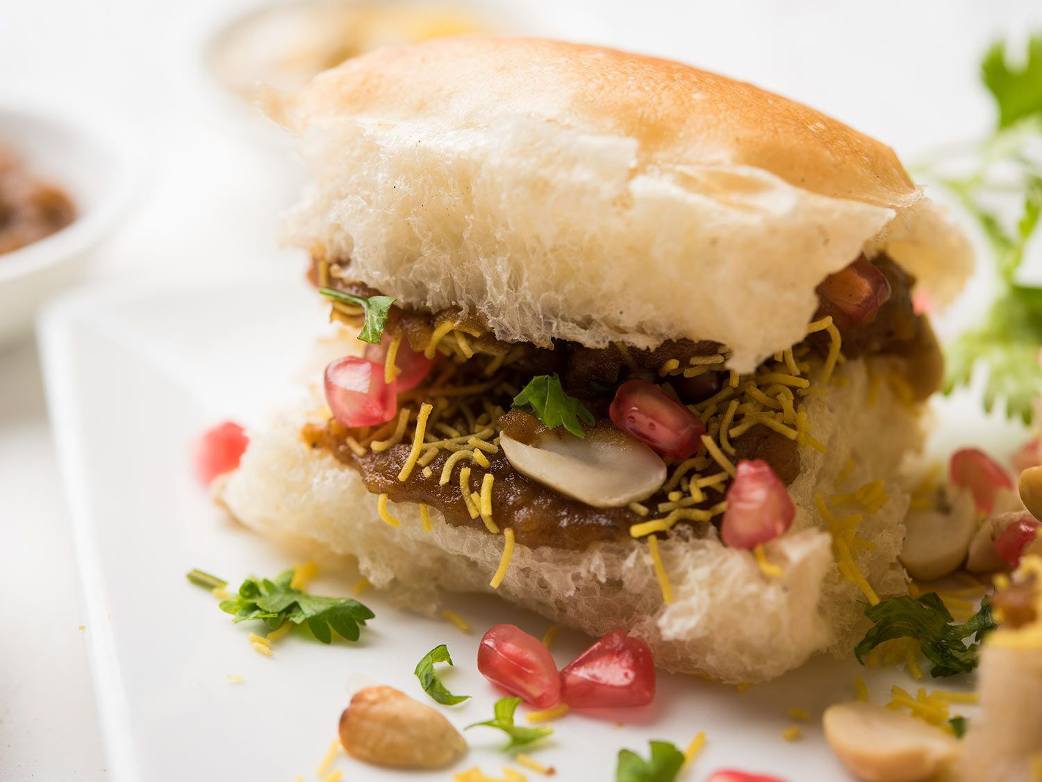 Dabeli: spiced potato mixture with chopped onions, coriander, coconut, peanuts, and pomegranate seeds in a soft white bun.