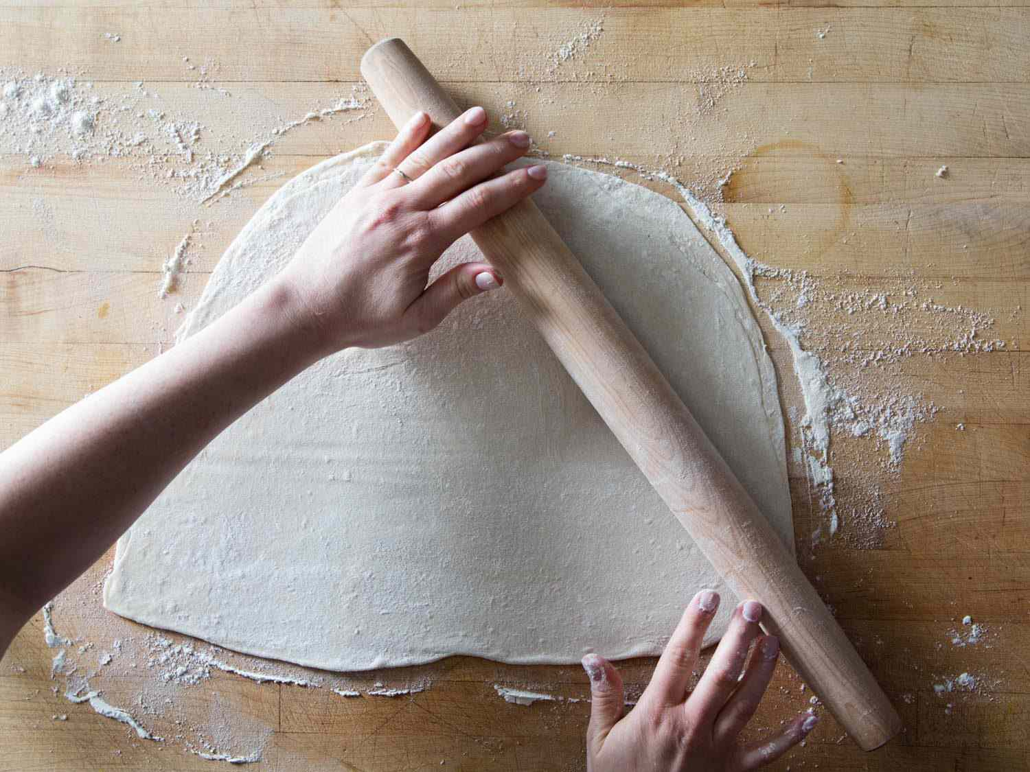 Rolling out dough for cannoli with a rolling pin