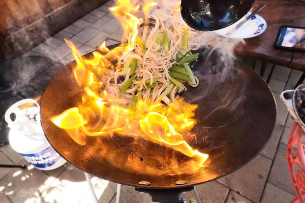 Food being tossed in wok with flames on an outdoor wok burner