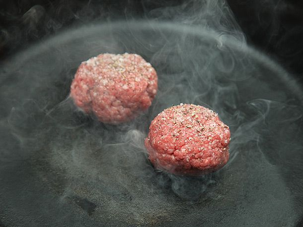 beef patties cooking on cast iron skillet