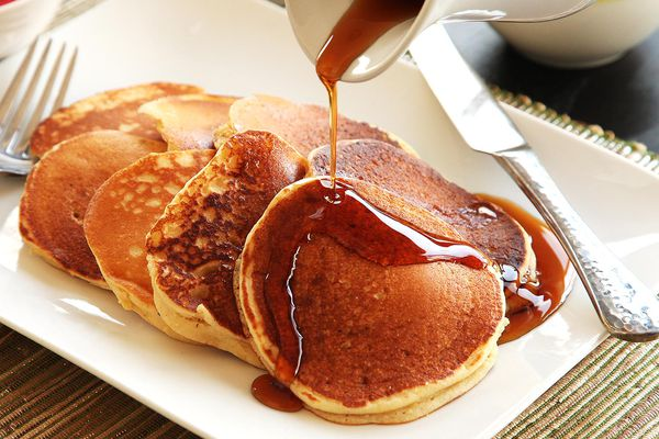 A white platter of light and fluffy buttermilk pancakes with maple syrup being poured over them.