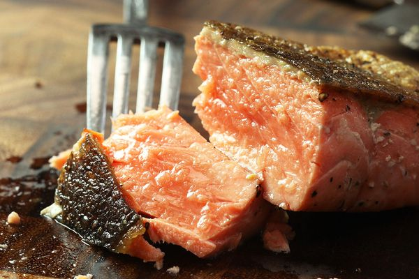 Using a fork to take a bite of a crisp-skinned seared salmon fillet on a wooden cutting board.