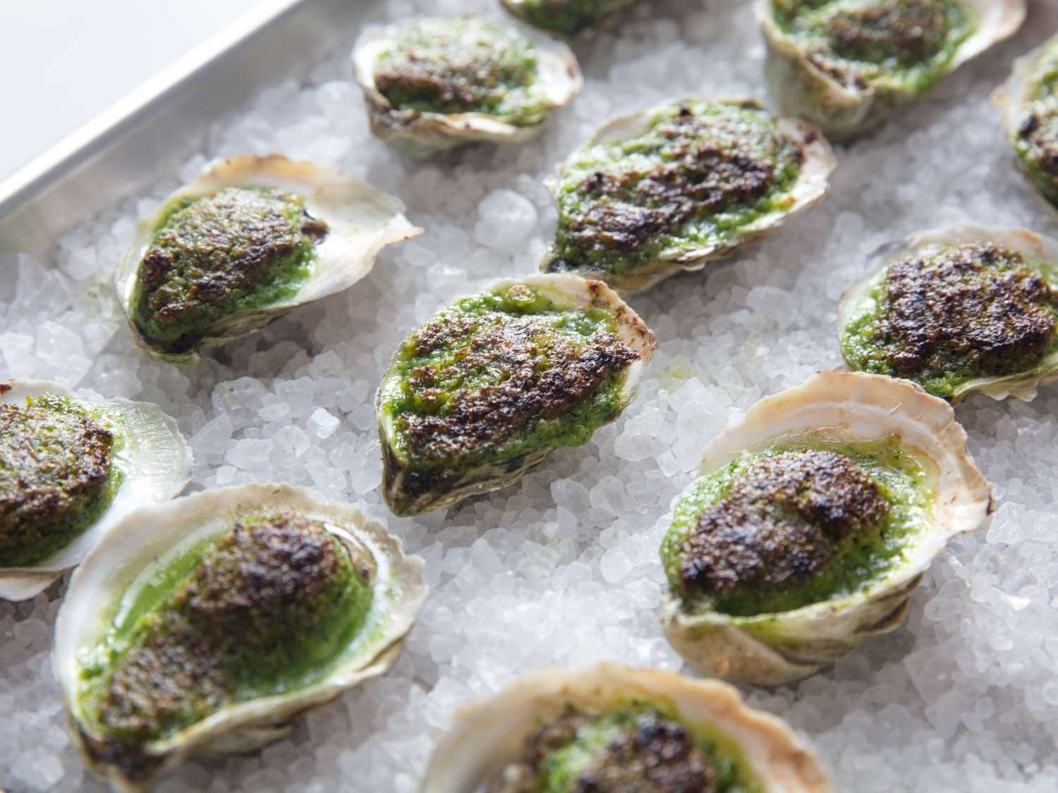 Oysters Rockefeller (broiled oysters with herb/butter sauce) lined up on a sheet pan