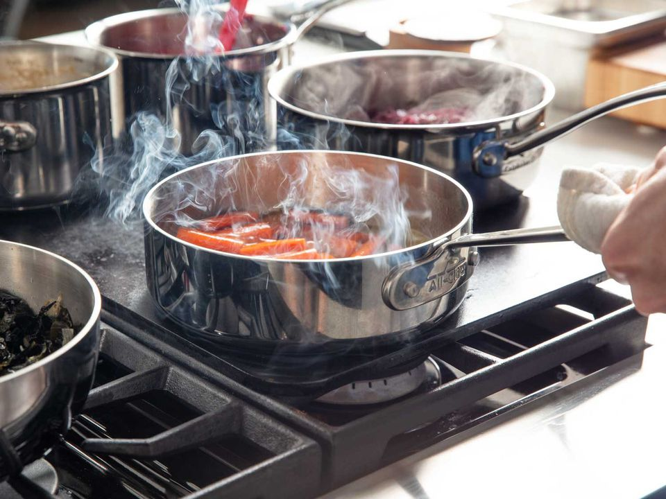 Cooking glazed carrots in a saucepan set on a Baking Steel on a gas range, with other saucepans of food warming at the same time.
