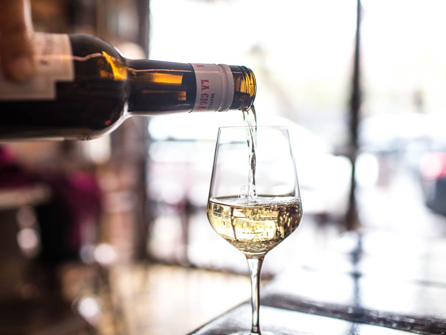 A hand pouring from a bottle of pale Manzanilla sherry into a wineglass
