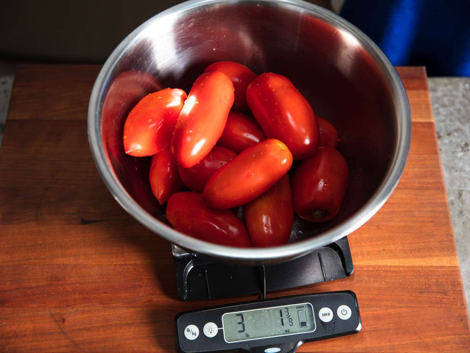 Washed plum tomatoes being weighed in a metal bowl on a digital scale
