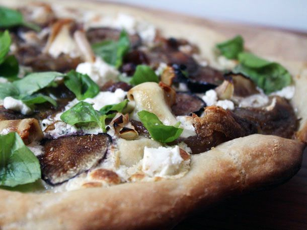 Pizza topped with pig's ears, figs, goat cheese, and basil.