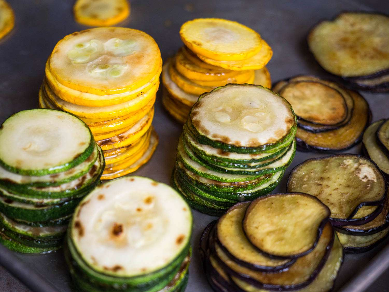 Stacks of cooked zucchini, yellow squash, and eggplant slices.