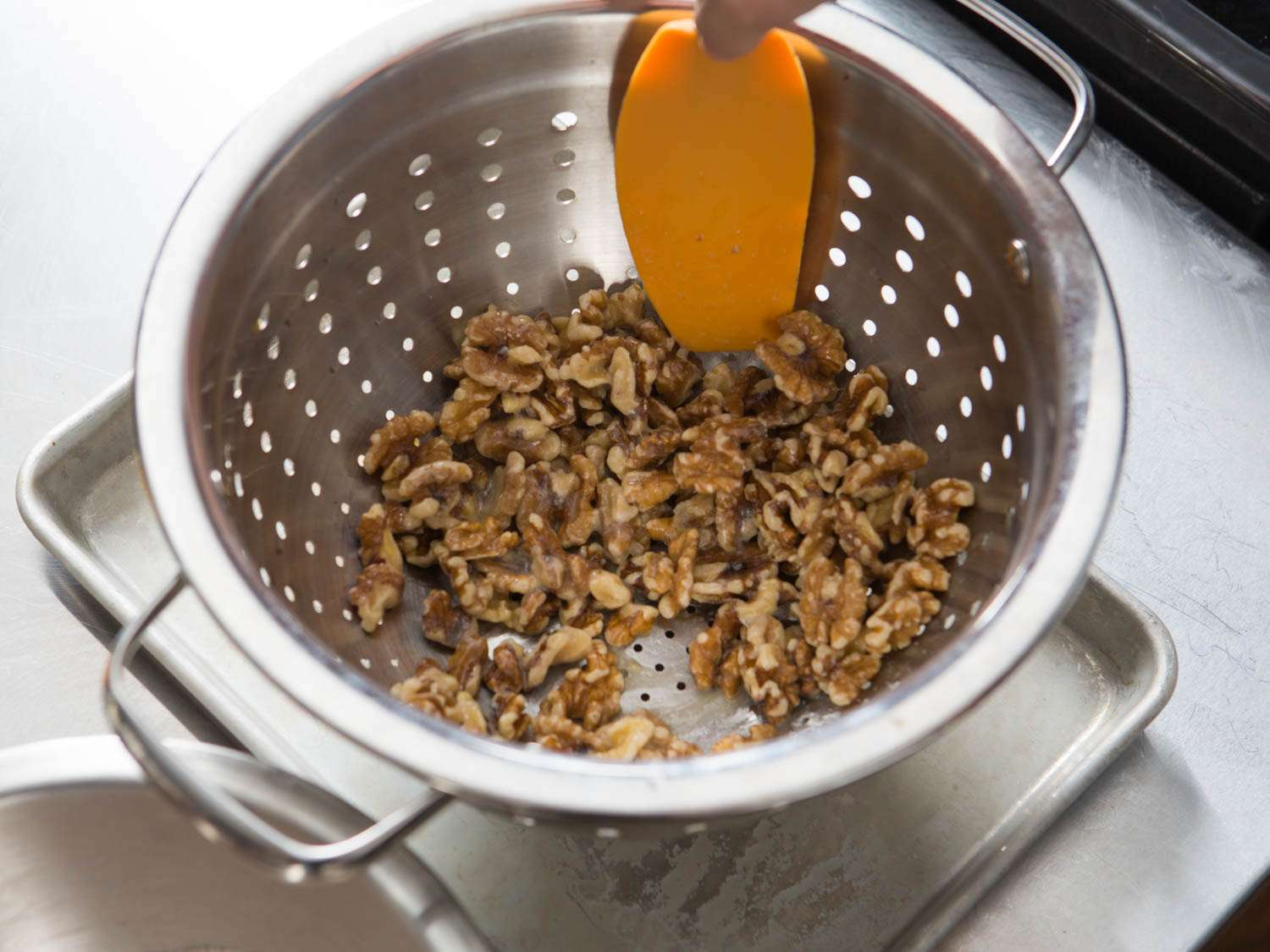 Draining egg white- and orange juice-coated walnuts in a colander.