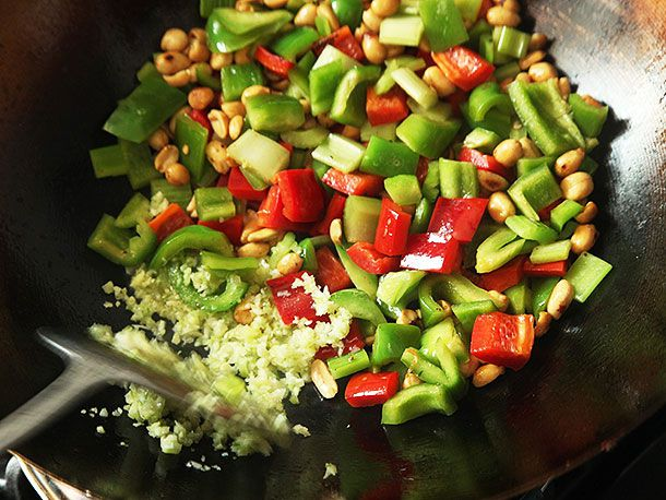 Adding minced garlic, ginger, and scallions to stir-frying peppers, celery, and peanuts in a wok for takeout-style kung pao chicken.
