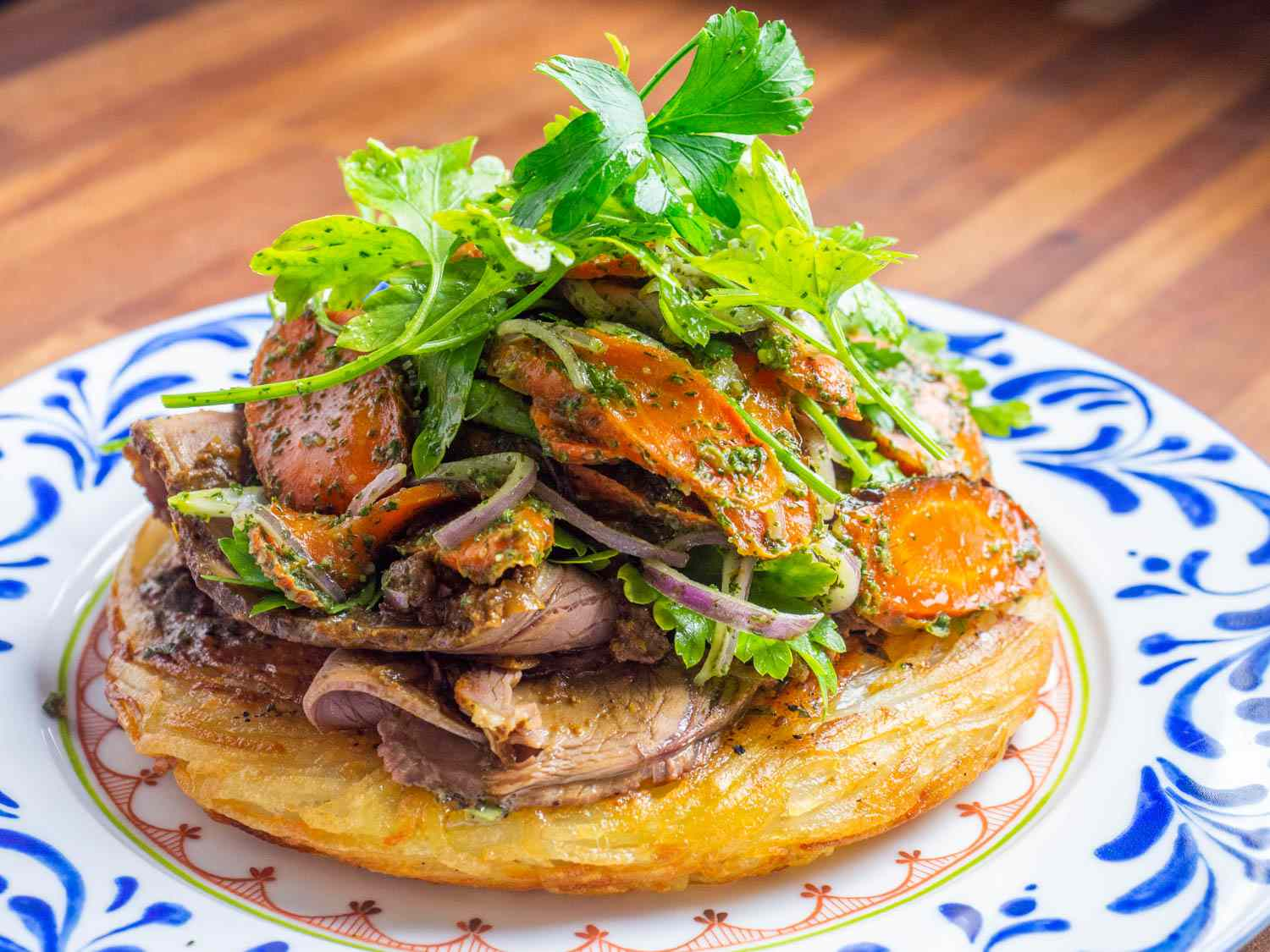 A potato cake topped with thinly sliced roasted lamb and a roasted carrot salad with fennel frond pesto