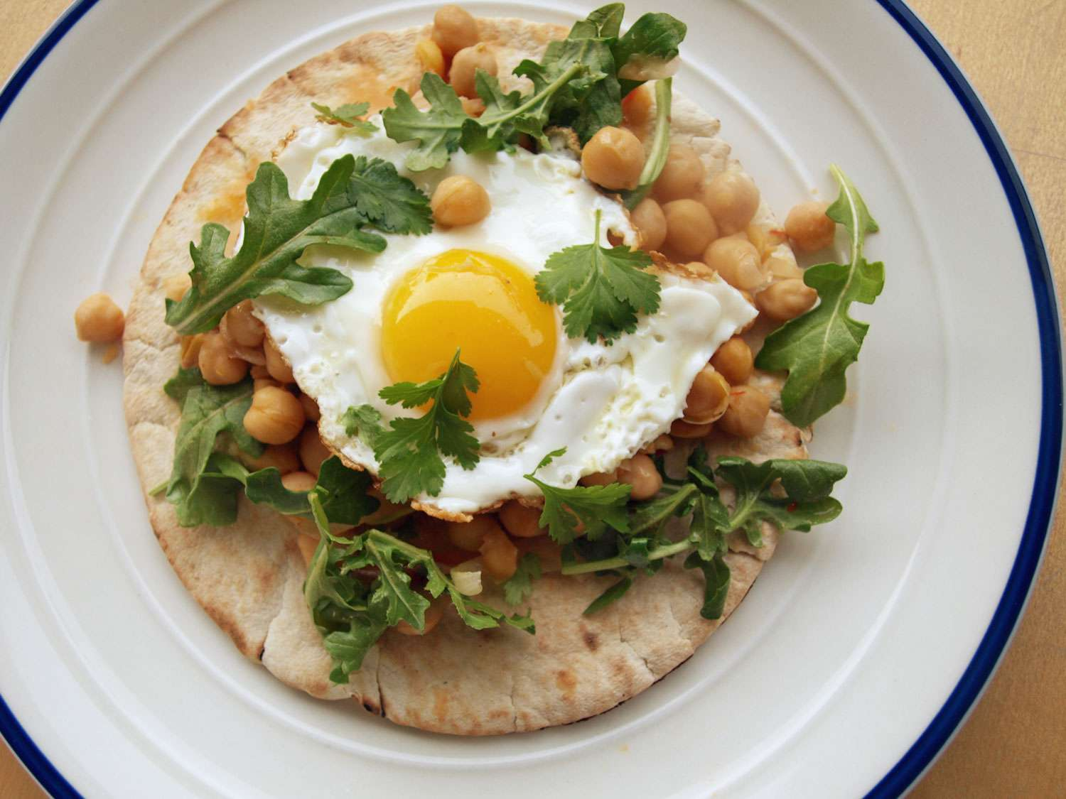 Harissa-spiked chickpeas on top of pita bread, topped with arugula, herbs, and a fried egg