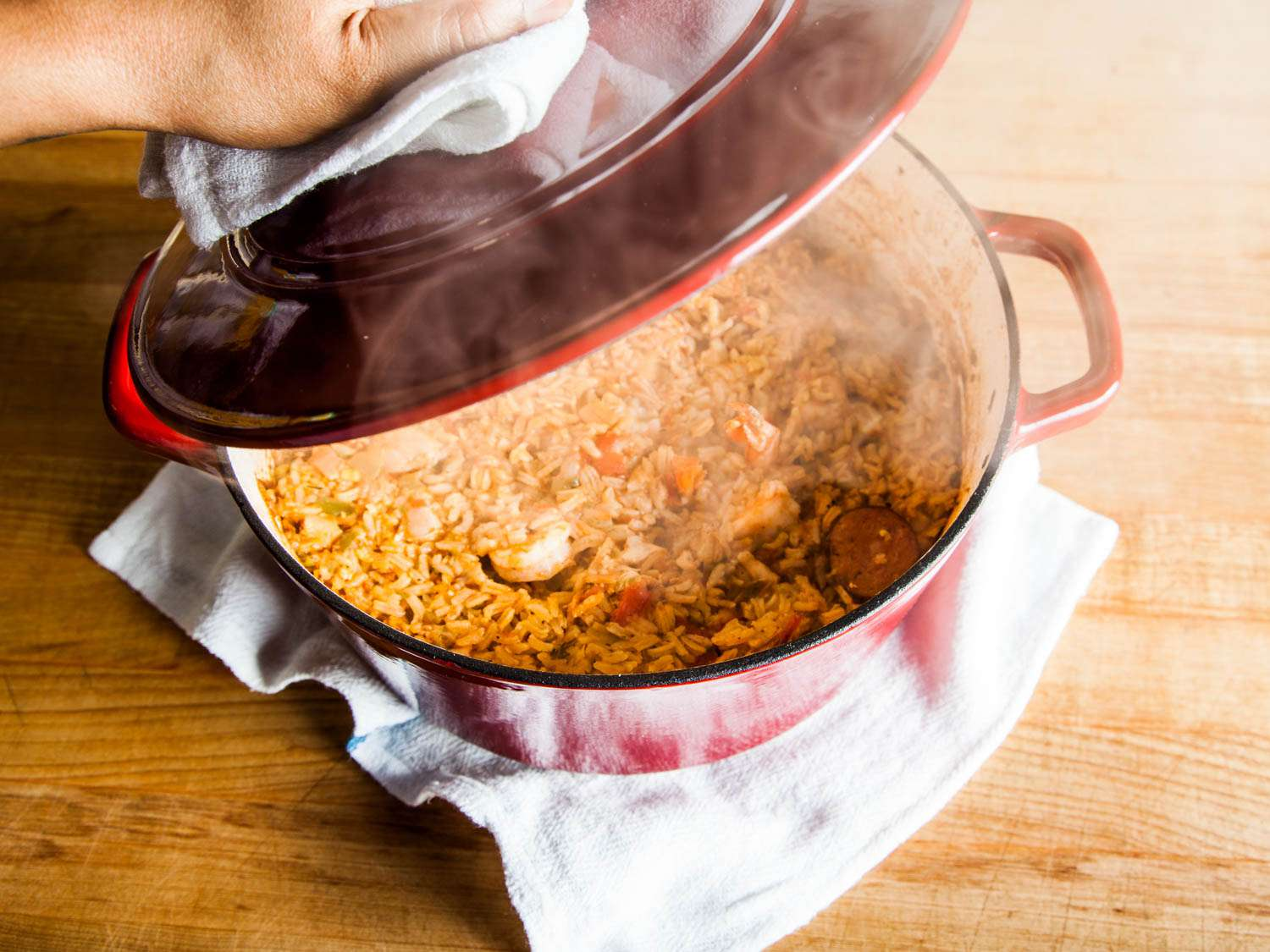 Lifting the lid of a Dutch oven containing steaming jambalaya
