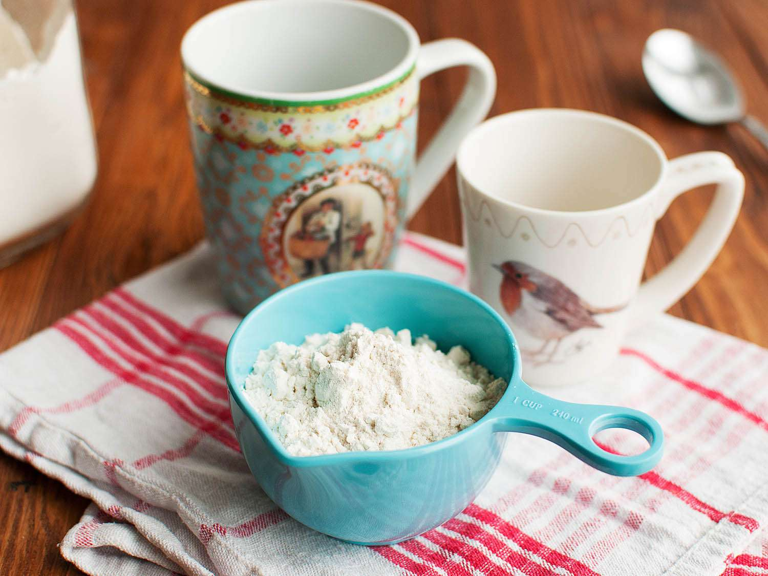 Measuring cups, one with flour in it