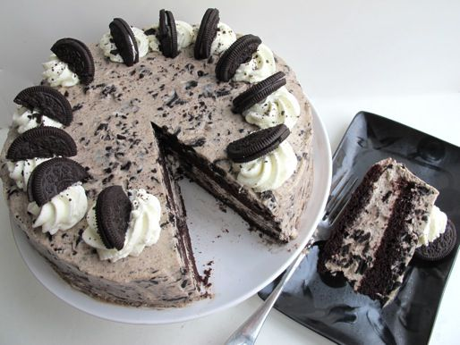 Chocolate Oreo cake on a cake stand with a slice removed and placed on a black plate.