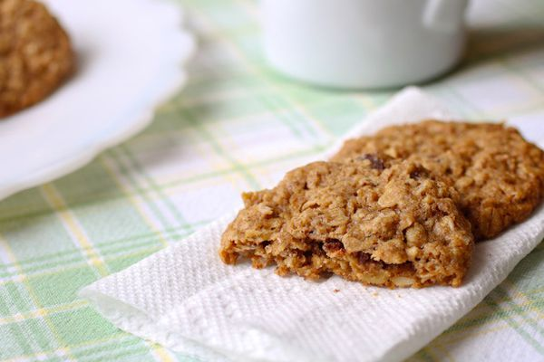 Gluten-free whole grain oatmeal cookies on a paper towel on a pastel plaid tablecloth.