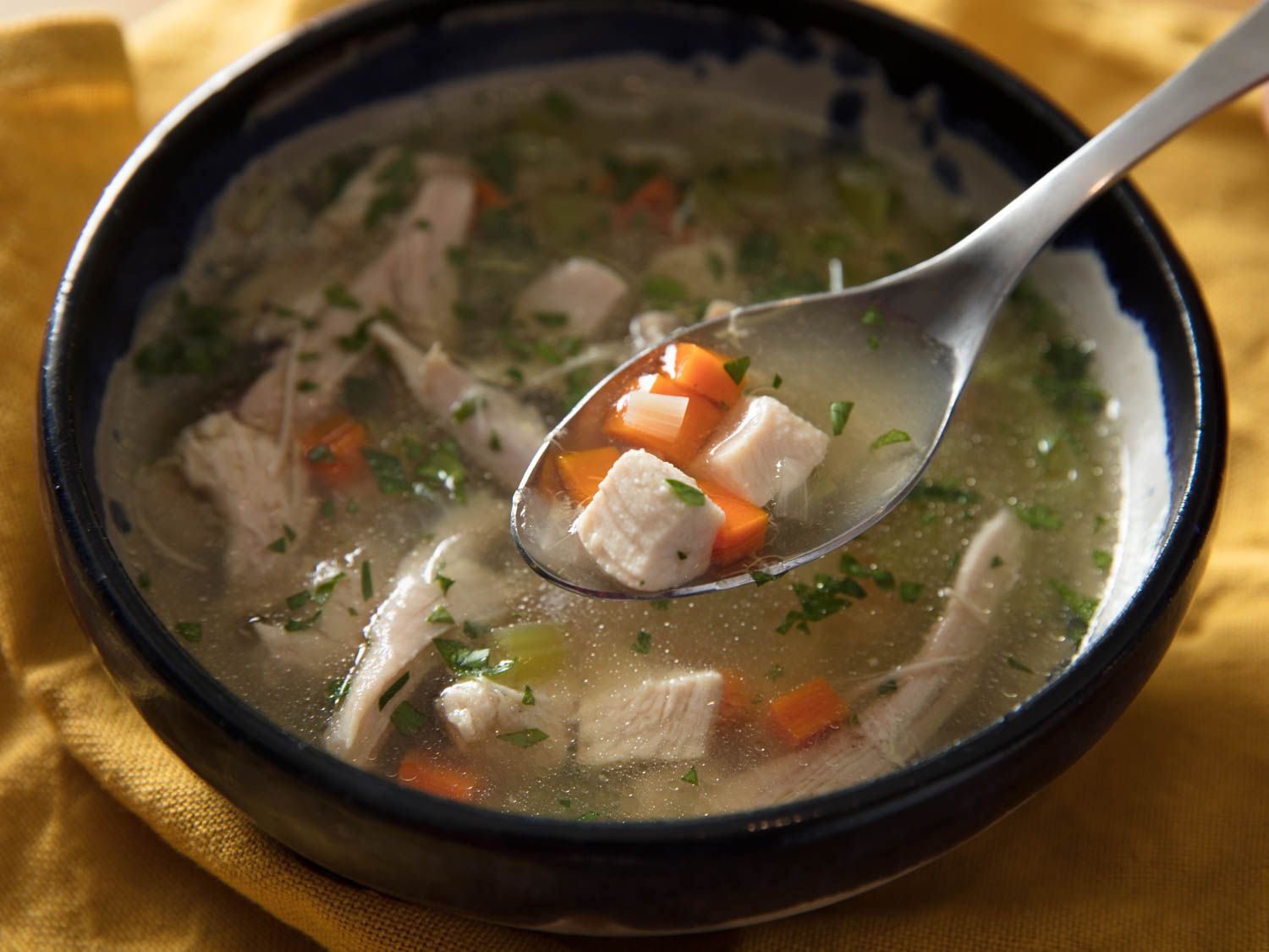 Close-up of a spoonful of chicken soup, with cubed chicken, carrots, and herbs