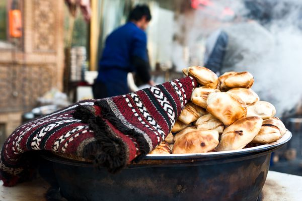 samsas, unleavened pockets of wheat dough that are filled with mutton, folded over like envelopes, and then baked in a deep outdoor pit