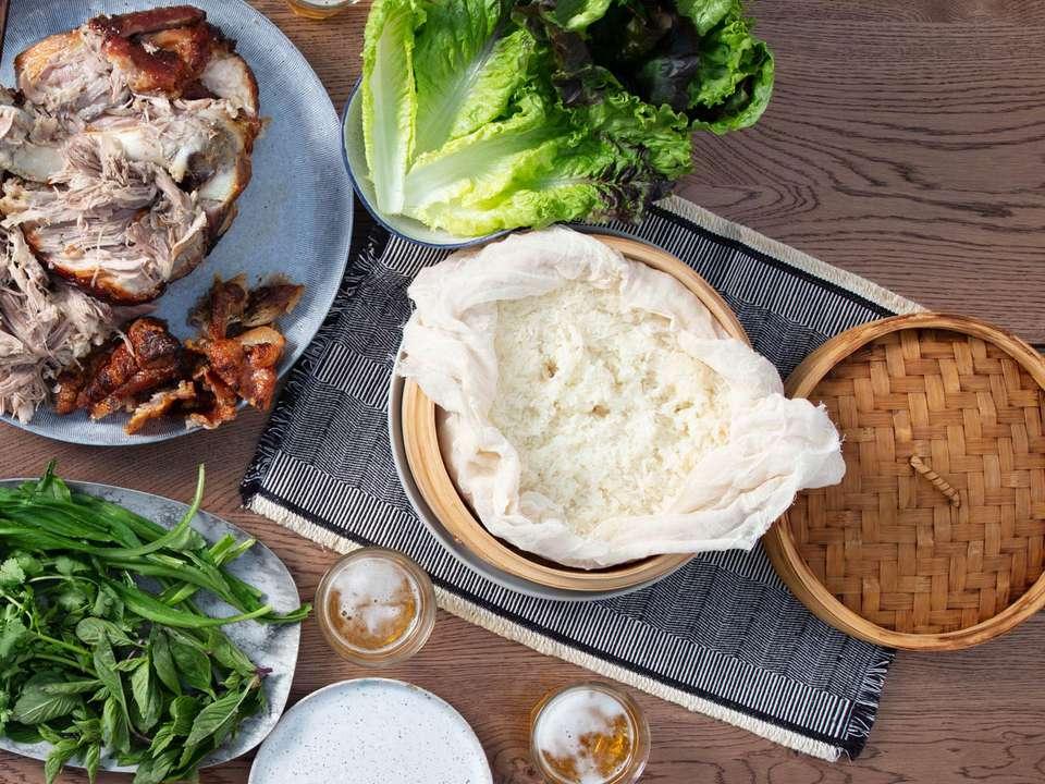 Overhead shot of a steamer basket full of sticky rice alongside a spread of roast pork shoulder, Thai herbs, and lettuces.