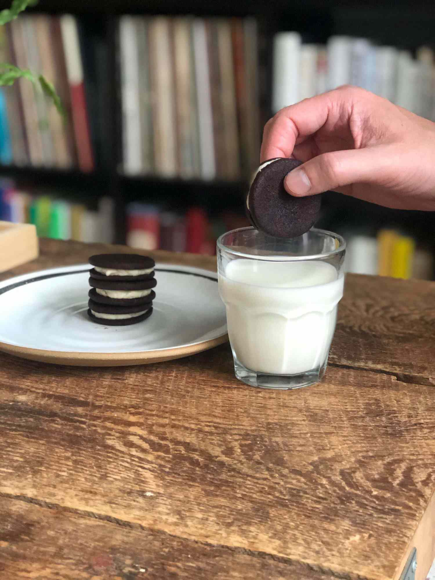 homemade oreo being dipped into glass of milk
