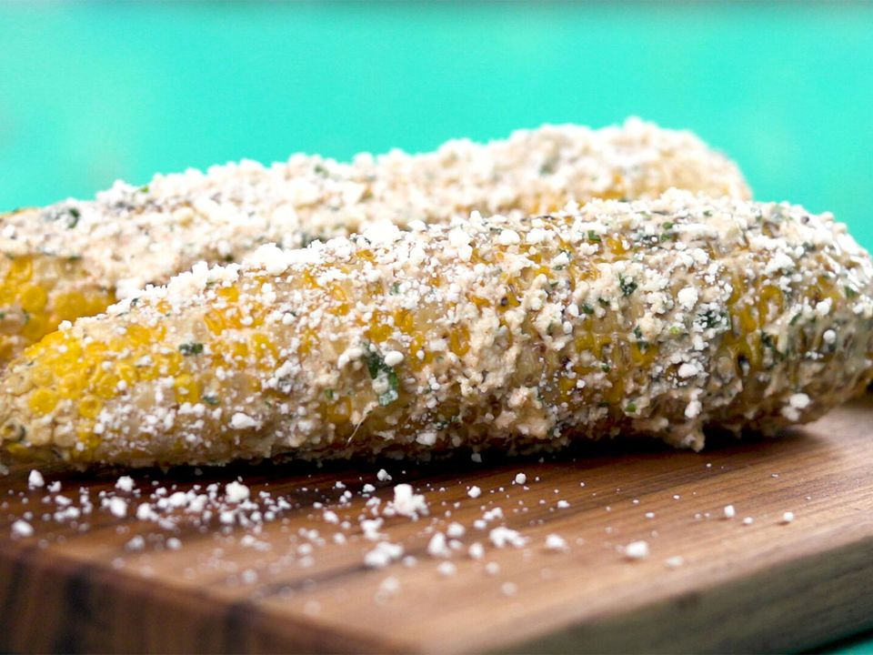 Elotes (Mexican street corn) topped with cheese on a cutting board.