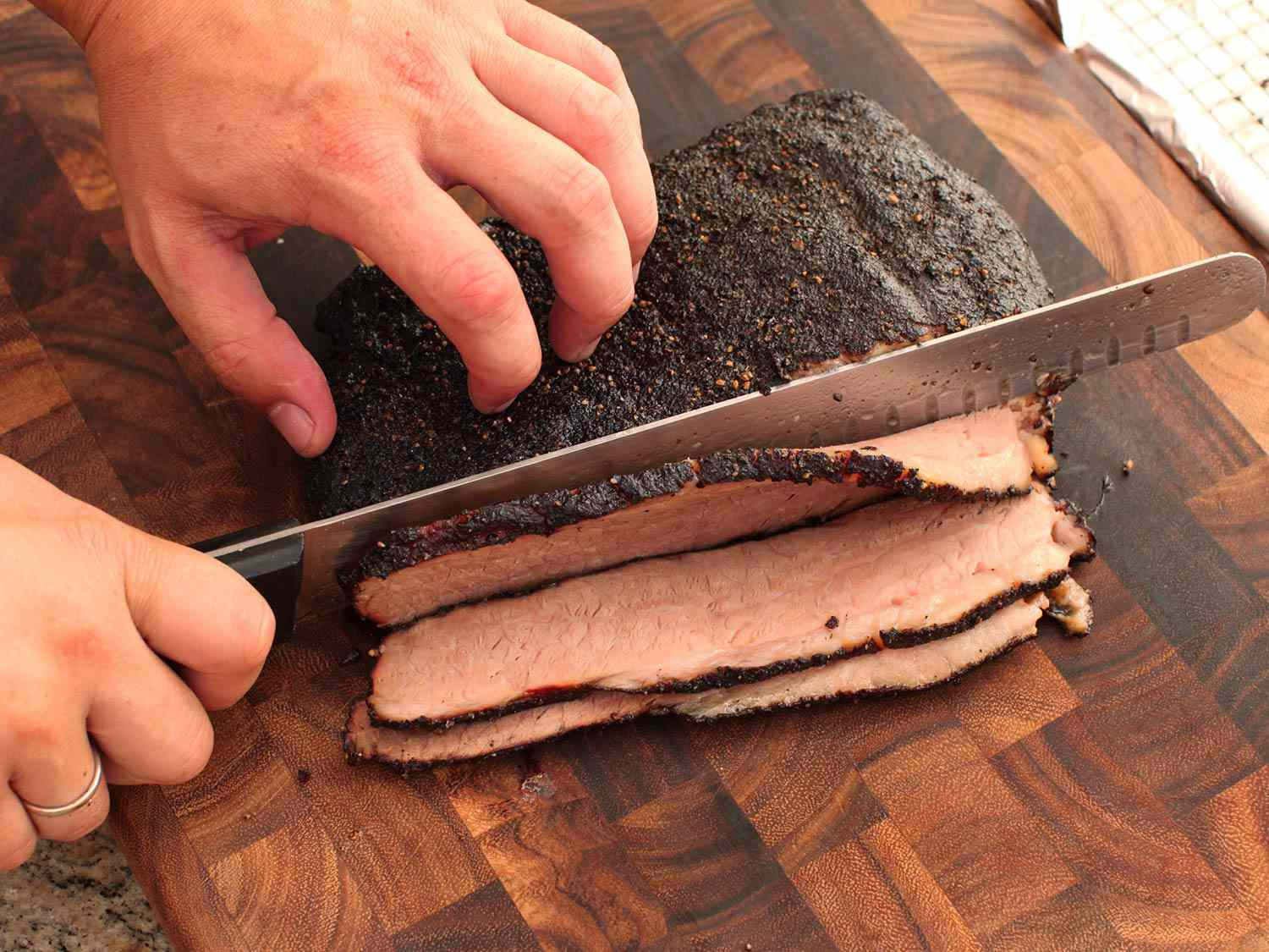 Cutting a finished brisket into slices on a wooden cutting board