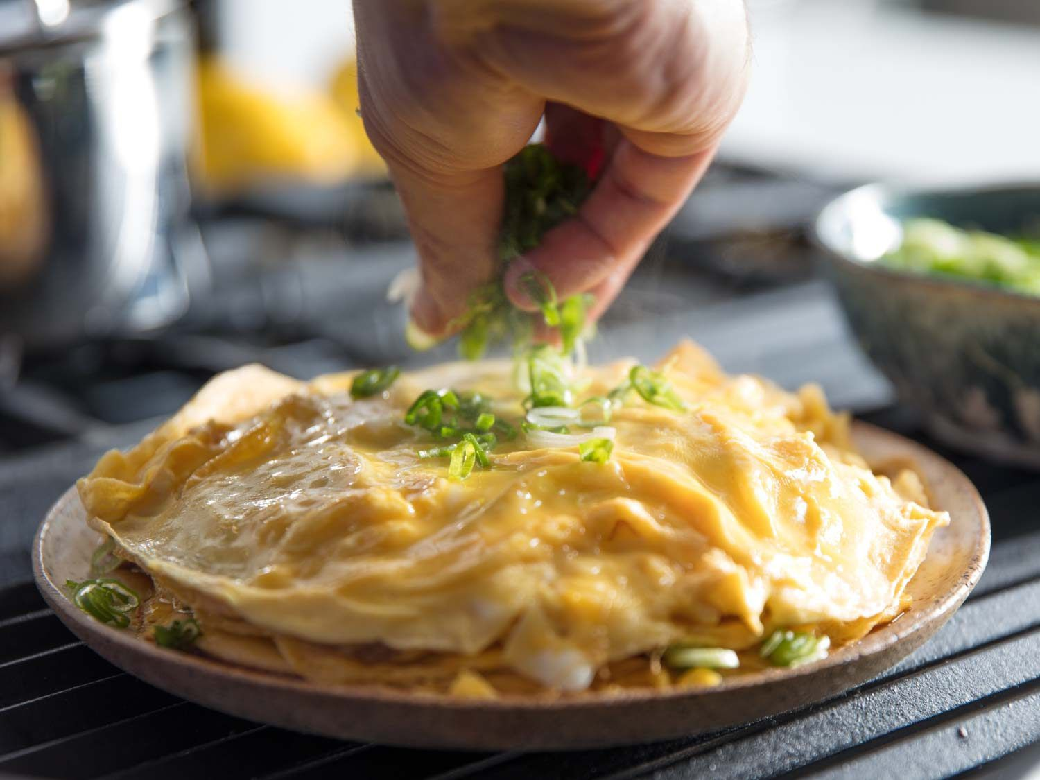 Scallions being scattered over Chinese-style layered omelette